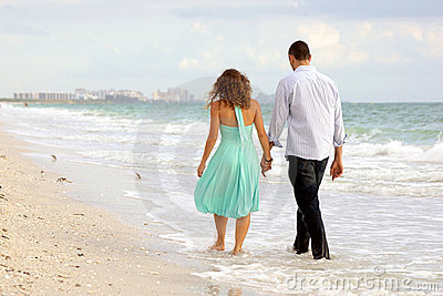 Pares jovenes que recorren de común acuerdo en el thi de la playa