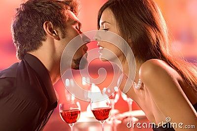 Pares jovenes que se besan en restaurante, celebrando o en d romántica
