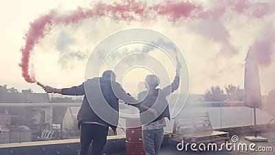 Pares jovenes que se divierten con humo coloreado en el tejado del edificio moderno Individuo joven con su caminar de la novia de metrajes