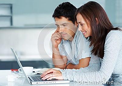 Pares jovenes que trabajan junto en la computadora portátil
