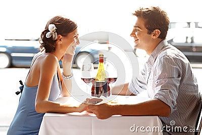 Pares jovenes románticos que se sientan en un restaurante