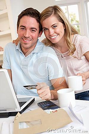 Pares jovenes usando de la tarjeta de crédito en el Internet