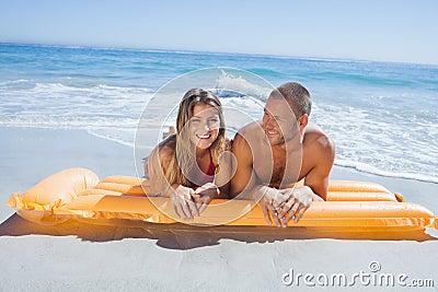 Pares lindos alegres en el traje de baño que miente en la playa