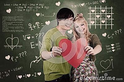 Pares lindos con la tarjeta del corazón de la tarjeta del día de San Valentín