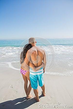 Pares loving que abraçam ao olhar o mar