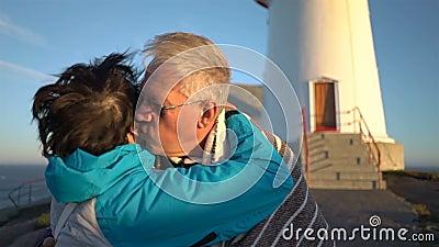 Pares maduros en la puesta del sol en la costa que se cubre con una tela escocesa del fuerte viento almacen de video