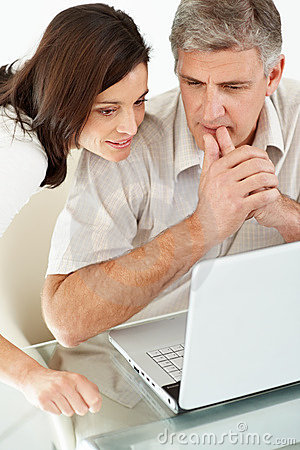 Pares maduros pensativos usando um portátil