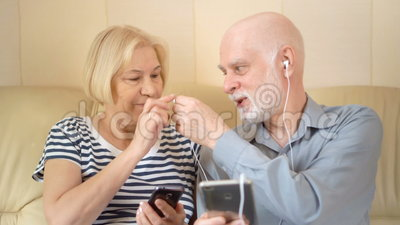 Pares mayores apuestos alegres que se sientan en el sofá Música que escucha en smartphone con los auriculares metrajes