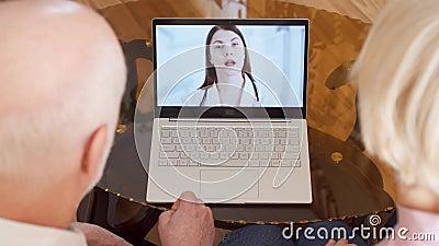 Pares mayores en casa que tienen consulta video de la charla vía llamada del app del mensajero en el ordenador portátil con el mé almacen de metraje de vídeo