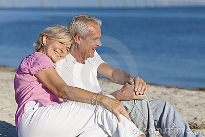 Pares mayores felices que se sientan junto en la playa