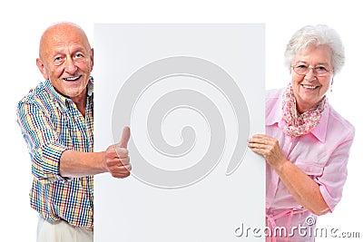 Pares mayores sonrientes felices con una tarjeta en blanco