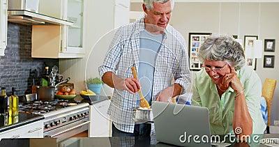 Pares mayores usando el ordenador portátil mientras que cocina en la cocina 4k almacen de video