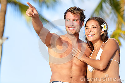 Pares na praia feliz no roupa de banho, apontar do homem