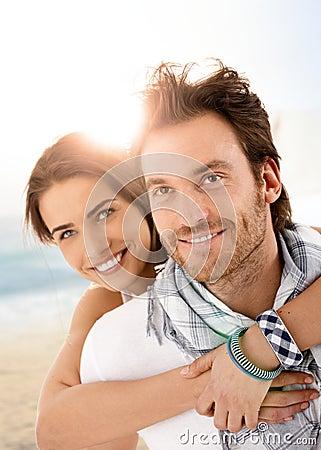 Pares novos felizes que abraçam na praia do verão