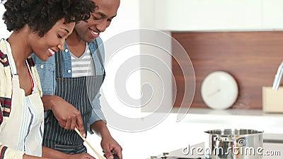 Pares novos felizes que cozinham junto