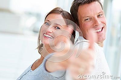 Pares novos felizes que mostram o polegar acima do sinal