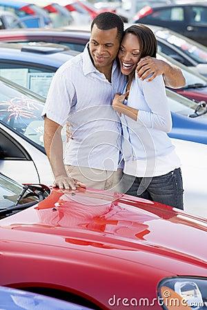 Pares novos que olham carros novos