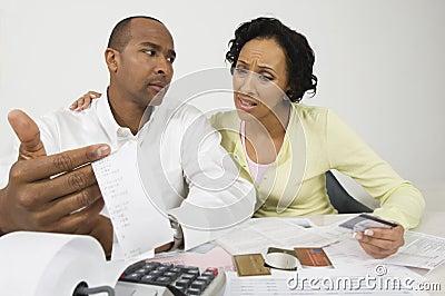 Pares preocupados com os cartões do recibo e de crédito da despesa
