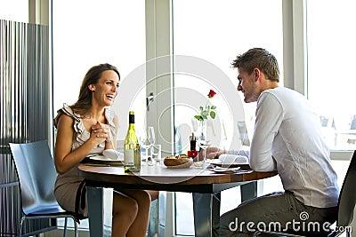 Pares que apreciam um jantar romântico para dois