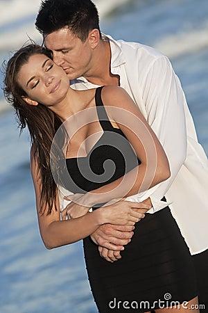 Pares que beijam no abraço romântico na praia