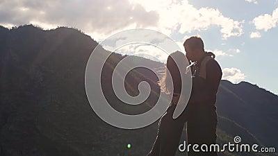 Pares que caminan contra el contexto de las montañas honeymoon beso en el fondo de las montañas el viento se convierte almacen de video