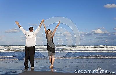 Pares que celebran los brazos levantados en una playa