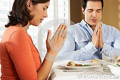 Pares que dizem a benevolência antes da refeição em casa