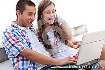 Pares que miran la computadora portátil junto