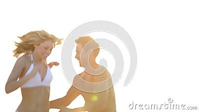 Pares românticos que correm na praia tropical bonita