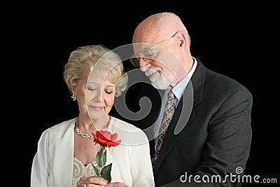 Pares sênior no preto - gesto romântico