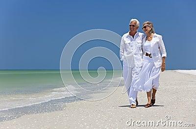 Pares sênior felizes que andam em uma praia tropical