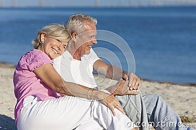 Pares sênior felizes que sentam-se junto na praia