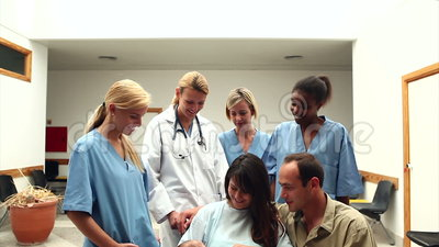 Pares sonrientes con su bebé recién nacido rodeado por un equipo de doctor almacen de metraje de vídeo