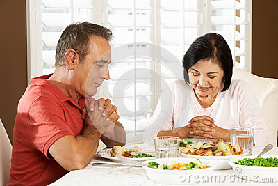 Pares superiores que dizem a benevolência antes da refeição em casa