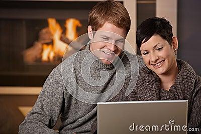 Pares usando la computadora portátil en el invierno