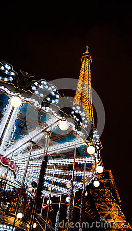 PARIS - DECEMBER 29: Eiffel Tower and antique carousel as seen at night on December 29, 2012 in Paris, France. The Eiffel tower is Editorial Stock Image