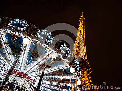 PARIS - DECEMBER 29: Eiffel Tower and antique carousel as seen at night on December 29, 2012 in Paris, France. The Eiffel tower is Editorial Photo