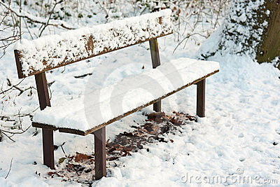 Park bench under pack of snow