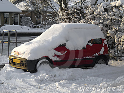 Parked red car under a layer of snow