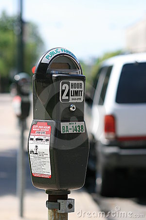 Parking meter against blurred car