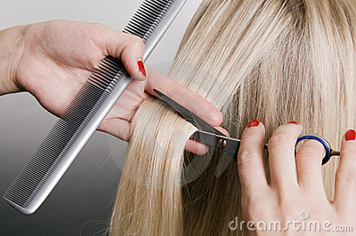 Parrucchiere che taglia capelli biondi