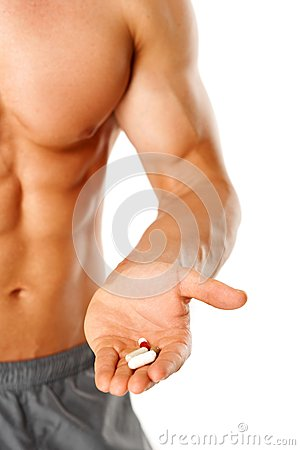 Part of muscular man torso with hand full of pills