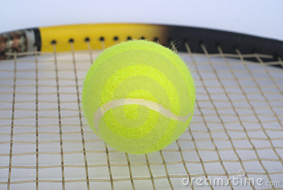 Part of tennis racquet with yellow ball clo