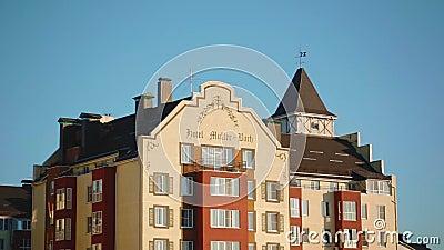Partie supérieure d'une intéressante maison-hôtel jaune-rouge avec un beau toit marron de style européen contre le ciel banque de vidéos