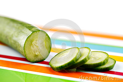 Partly sliced organic cucumber on a stripy colorful ceramic plate
