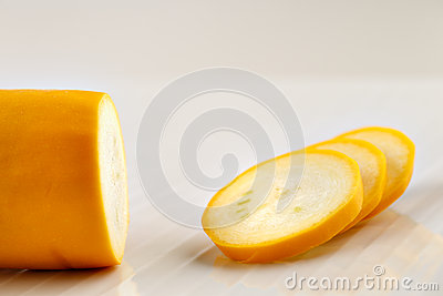 Partly sliced yellow zucchini courgette on a white ceramic plate