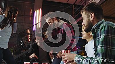 Party-Atmosphäre in einer stilvollen Loft-Gruppe von Freunden feiern etwas, während sie auf dem Sofa sitzen und einige nehmen ein stock video footage