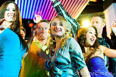Party people dancing in disco or club