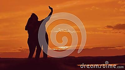 Pary sylwetka robi selfie outdoors Mężczyzna i dziewczyna najlepszy przyjaciele bierze selfie podczas zmierzchu Nowożytny pojęcie zbiory