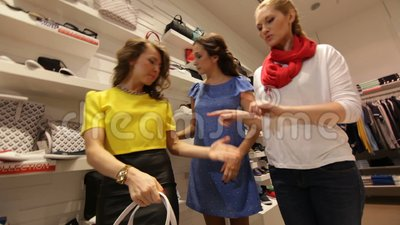 Paseo de las mujeres a lo largo de la tienda de la moda y mirada en el bolso metrajes